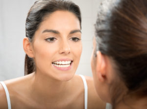 woman looking at white teeth in mirror