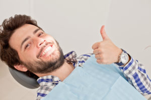 man thumbs up in dentist chair