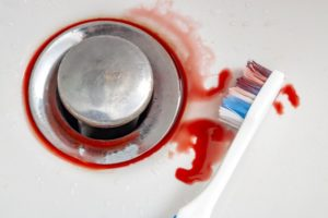 toothbrush in a sink with blood on it