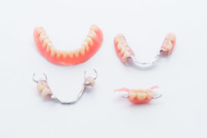 Set of full and partial dentures on white background